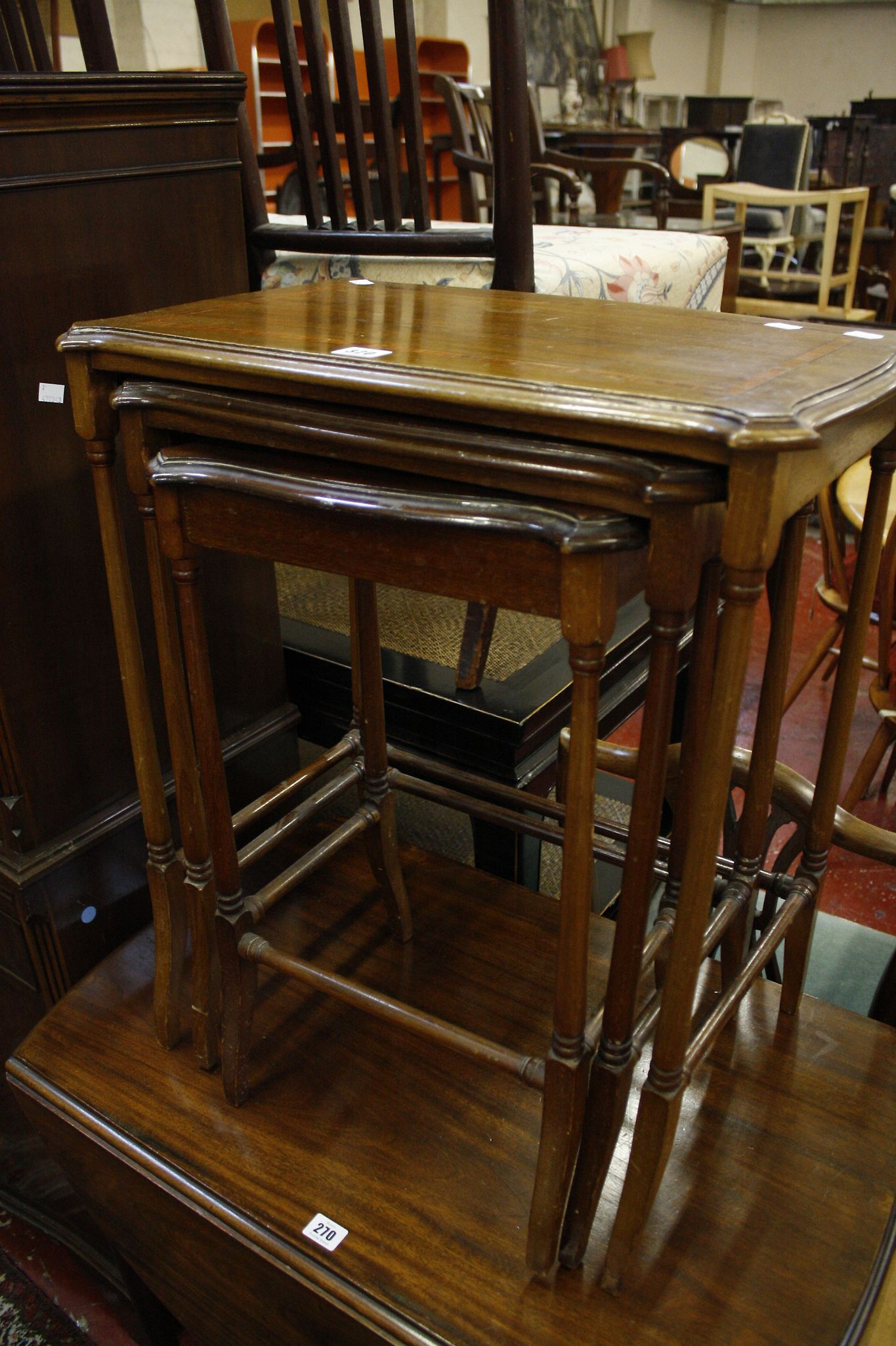 A nest of three Edwardian mahogany tables with rosewood banding