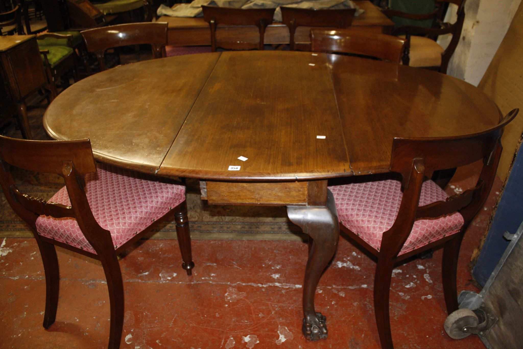 A mahogany oval dropleaf dining table
