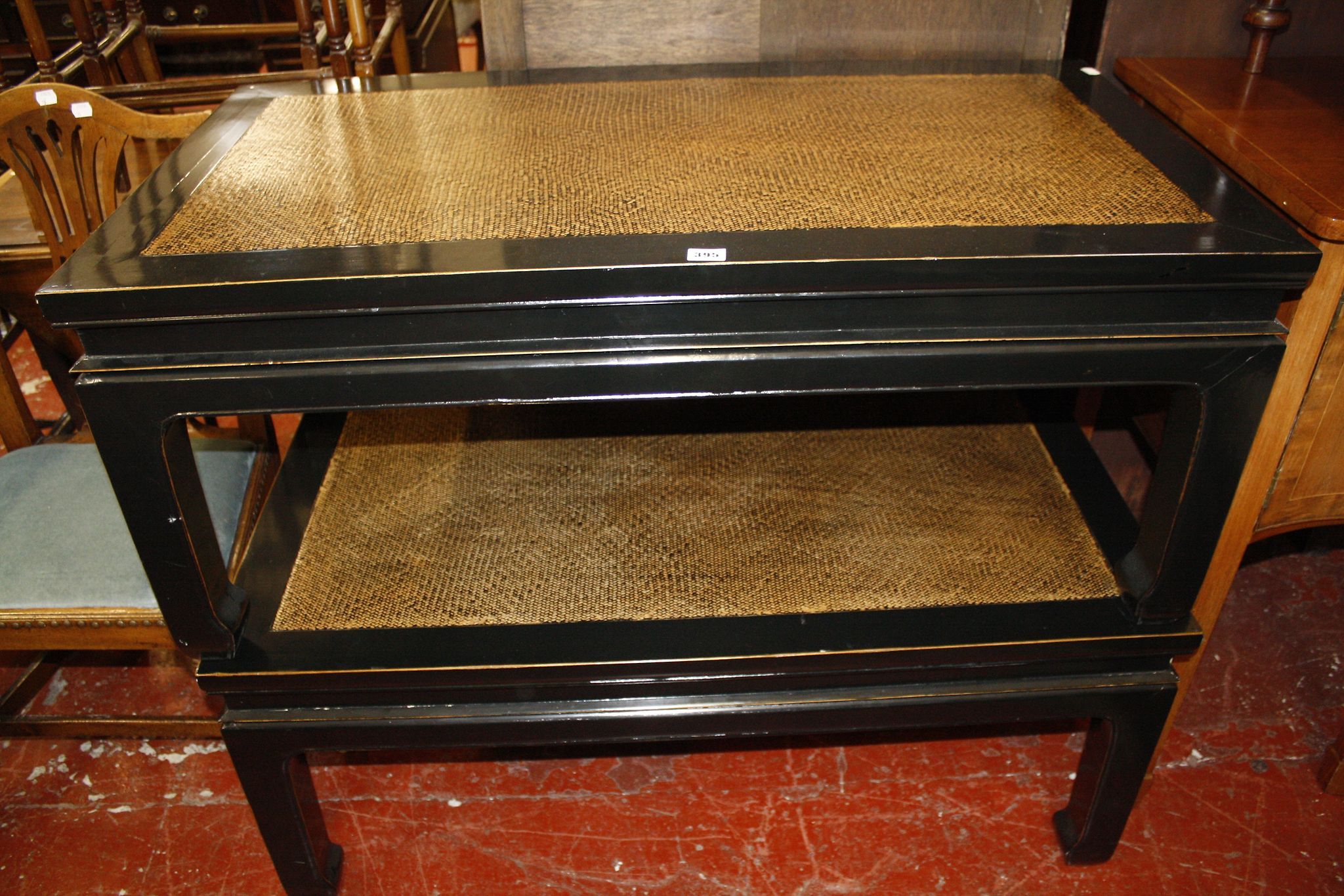 A pair of ebonised and caned coffee tables