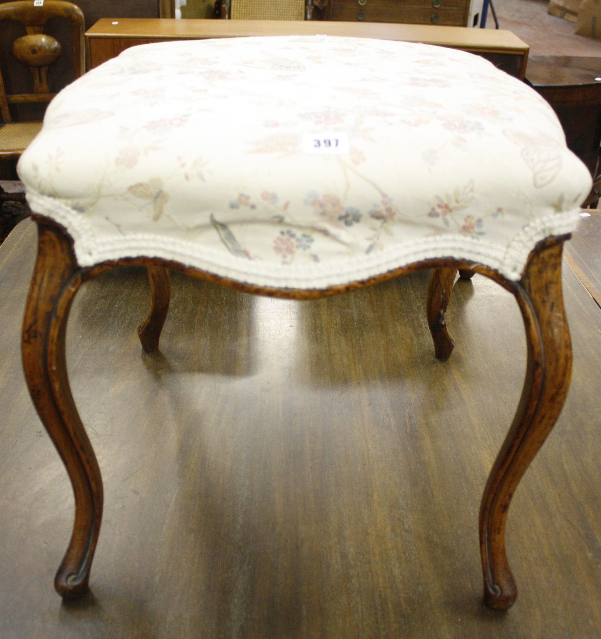 An upholstered stool on cabriole legs