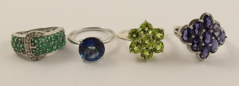 A collection of four silver rings set with emeralds, diamonds, peridot and other gems