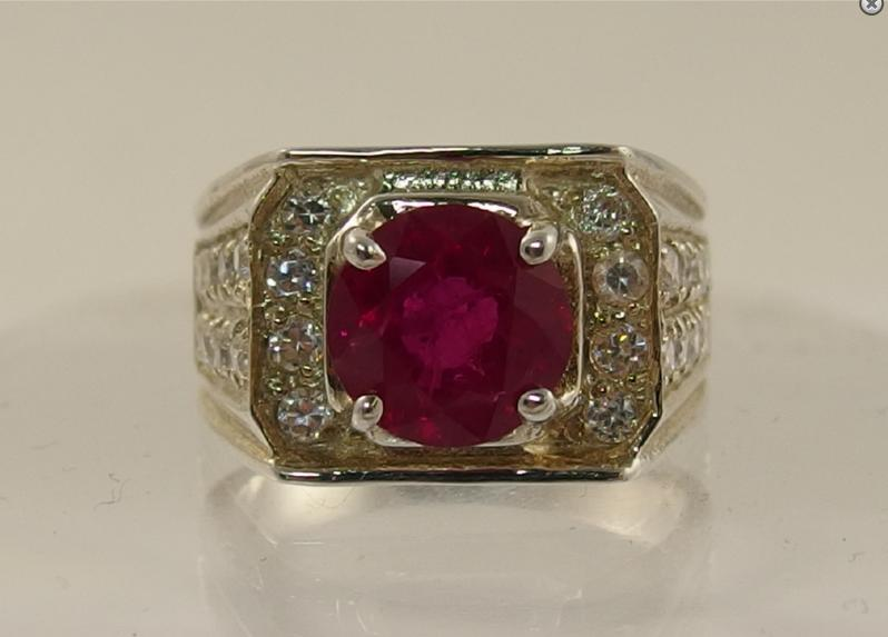 A silver ring set with a ruby and clear topaz gem stones
