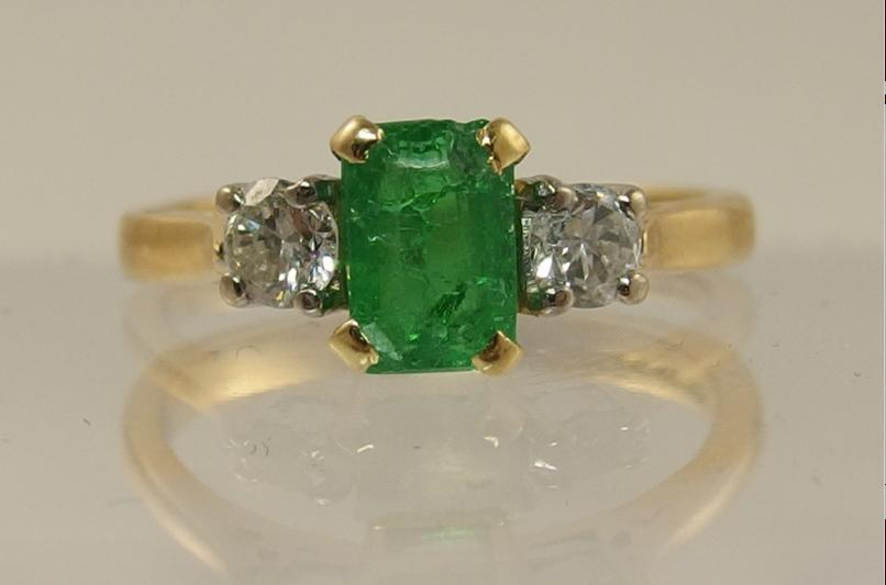 An 18ct gold emerald and diamond ring