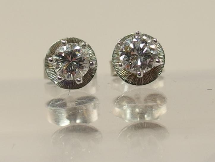 A pair of 14ct white gold diamond stud earrings combined diamond total 0.50cts