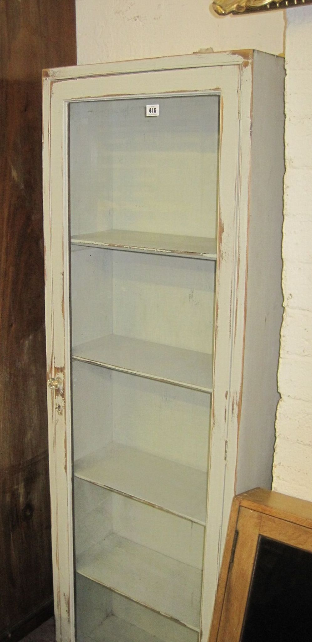 A painted display cabinet enclosing shelves