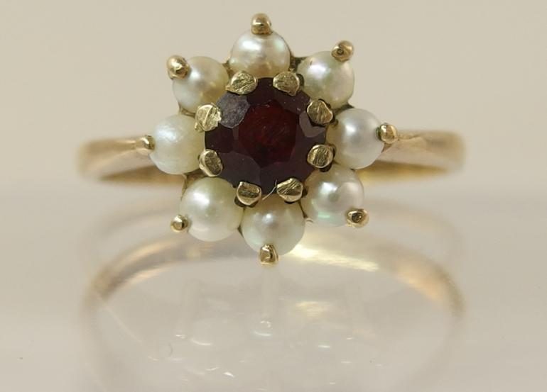 A 9ct garnet and pearl flower ring