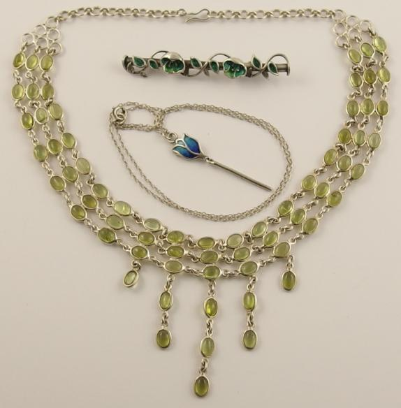 A white metal peridot festoon necklace, a Norman Grant enamelled pendant and an enamelled flower brooch
