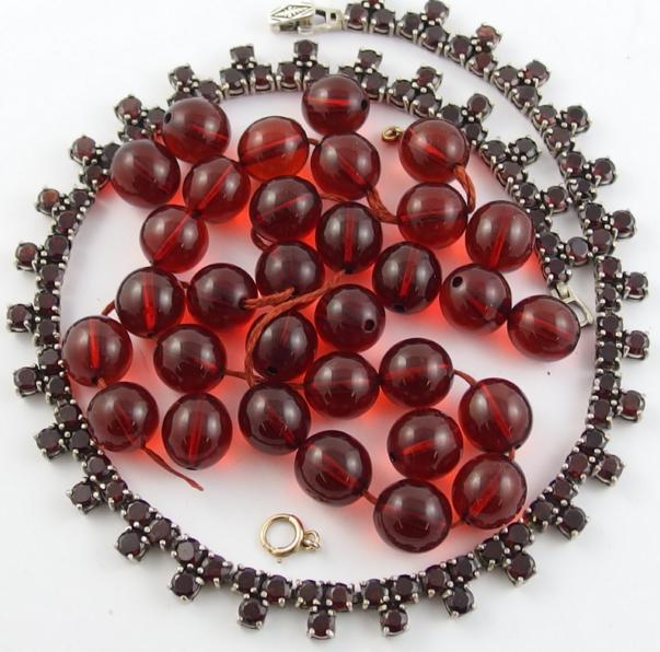 A silver garnet set necklace and a string of cherry amber coloured beads