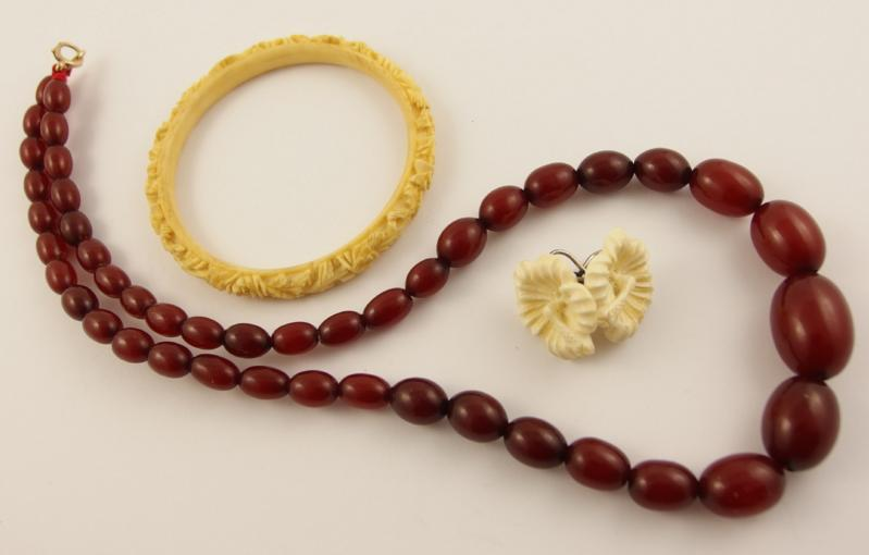 A string of cherry amber coloured beads and some carved bone items