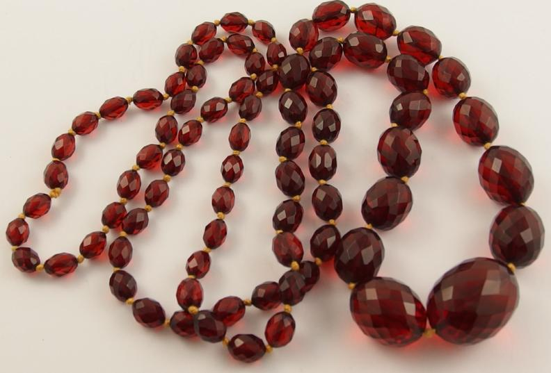 A string of faceted cherry amber coloured beads