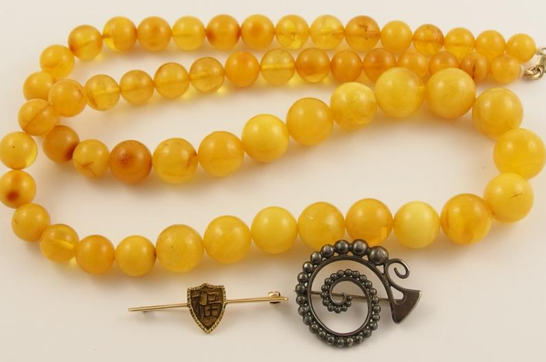 A string of yellow amber coloured beads, a Chinese gold brooch and a silver brooch possibly by Malcolm Grey
