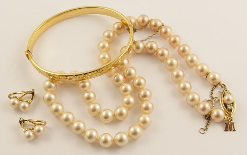 A good string of Majorica faux pearls with matching earrings with a silver clasp and a gold plated bangle
