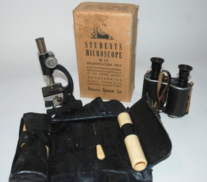 A pair of prism binoculars, a students microscope and part ivory gents toiletry set