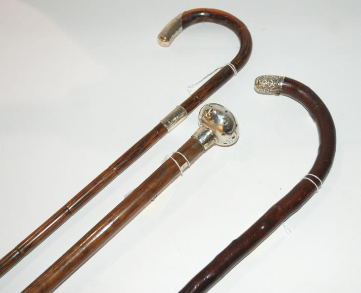 A silver tipped walking stick and two other white metal examples