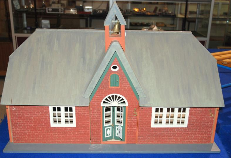 A model of a country school house with hinged panels to front and side revealing interior