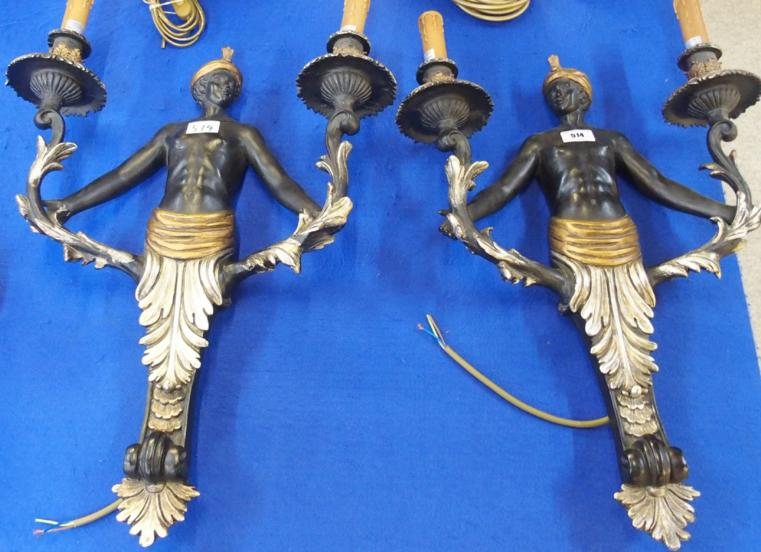 A pair of figural wall mounted lamps.