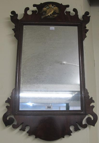 An Edwardian mahogany wall mirror with gilt carved bird to top