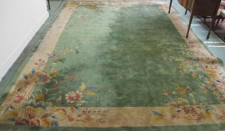 A large floral carpet on a green and cream ground, 14 1/2ft x 10ft
