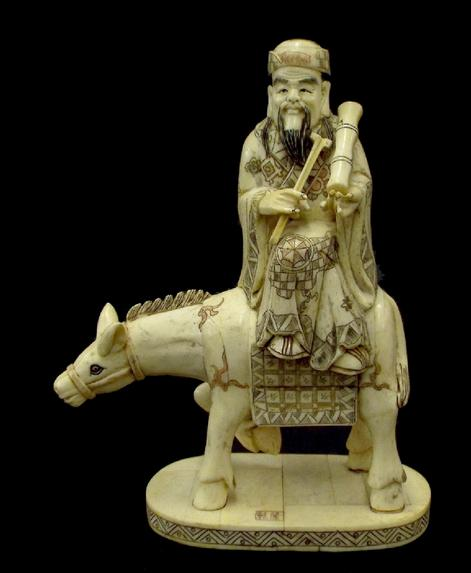 Chinese carved bone okimono of a sage on the back of a donkey, with polychrome highlights, calligraphy signature to base