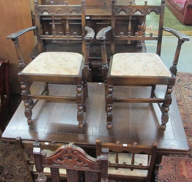 An Ercol oak Jacobean style extending dining table, six chairs and a Jacobean style sideboard
