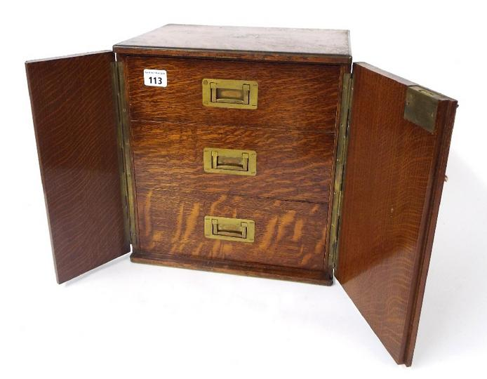 Good antique oak table top specimen cabinet with twin campaign type handles and twin doors enclosing three interior drawers