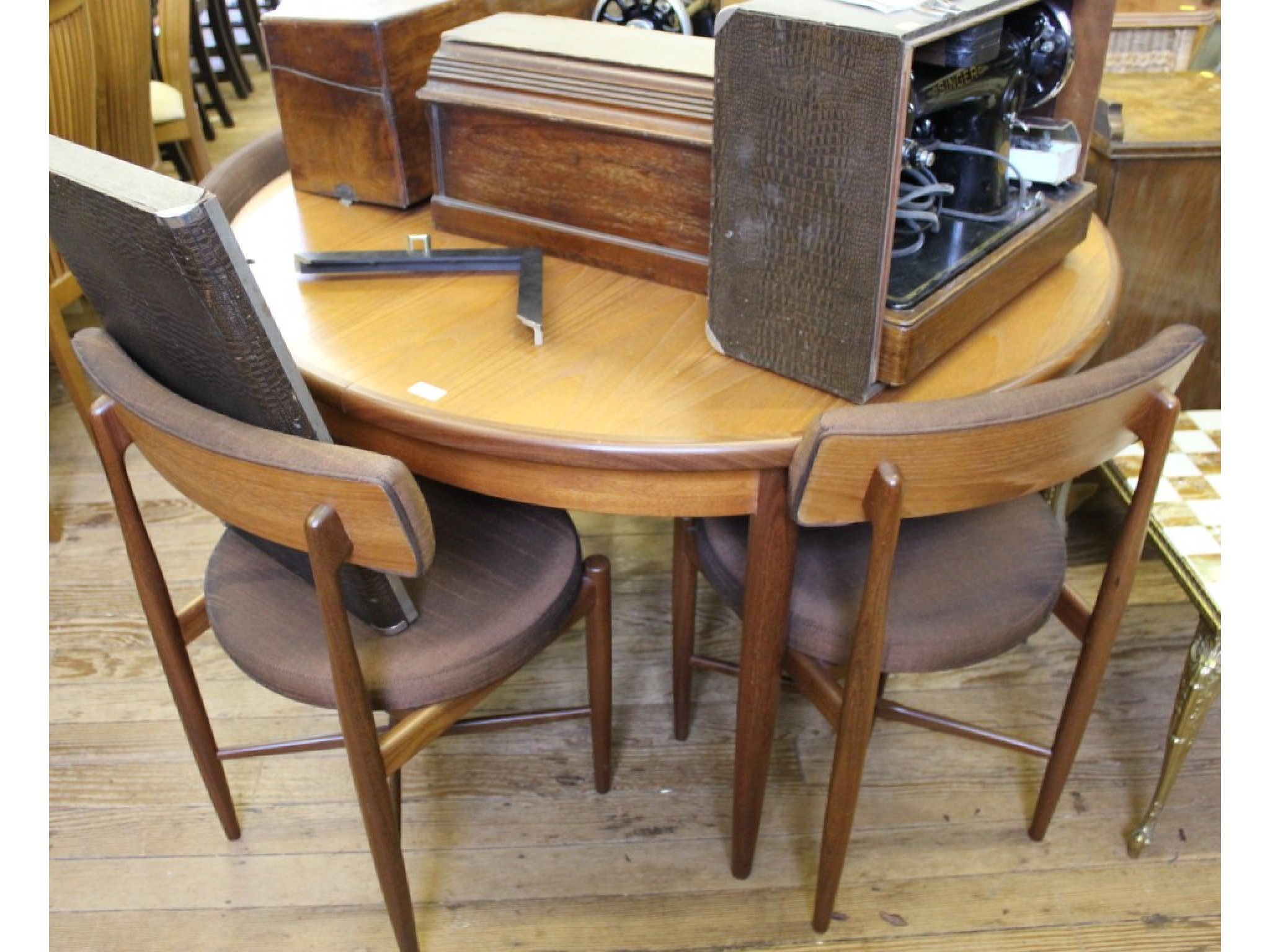A set of four G-Plan teak chairs with padded backs and seats, and a circular extending dining table
