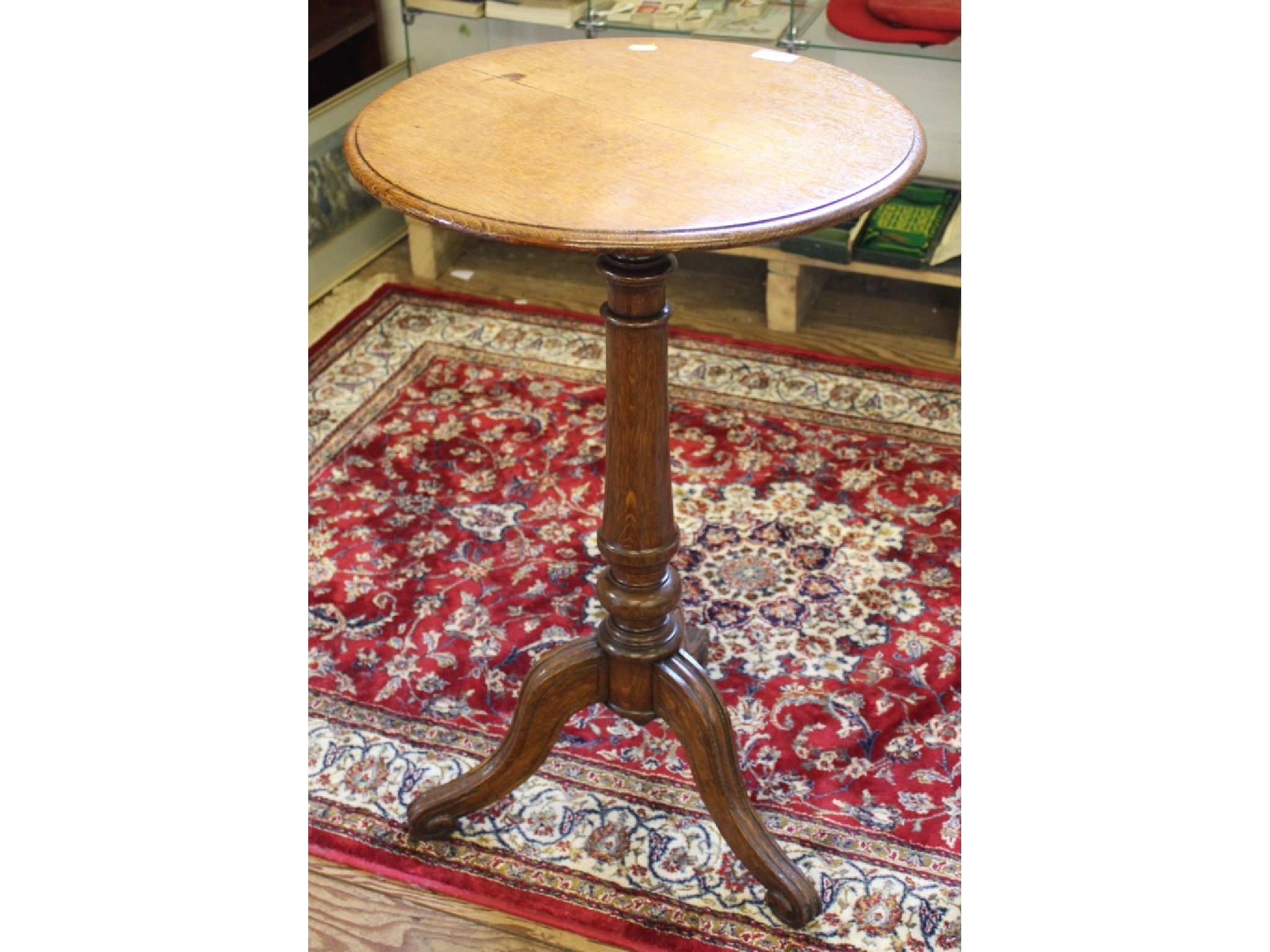 An oak tripod table, with circular top, turned stem and moulded legs