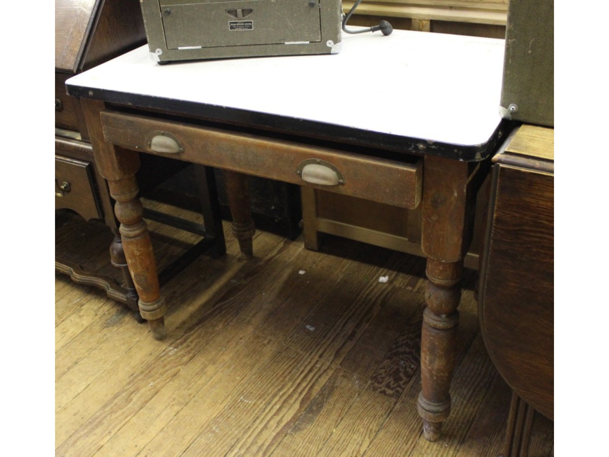 A pine kitchen table with tin top, frieze drawer and turned legs