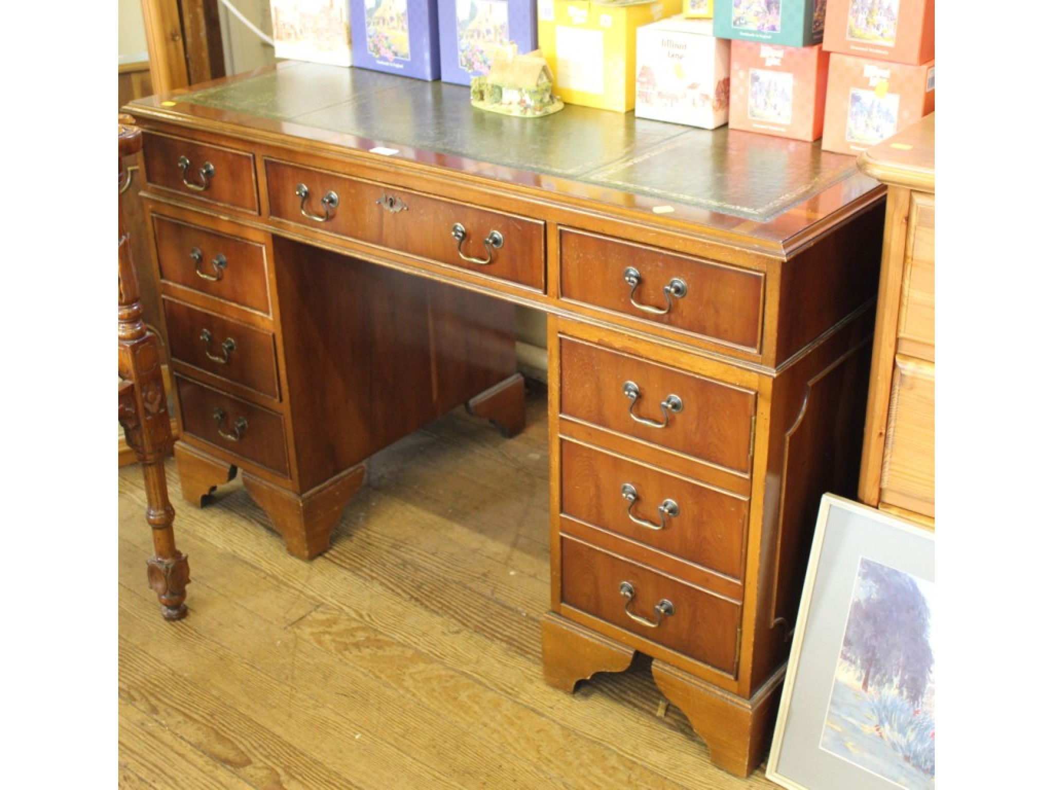 A pedestal desk with green leather top, three top drawers, three left drawers and cupboard to right