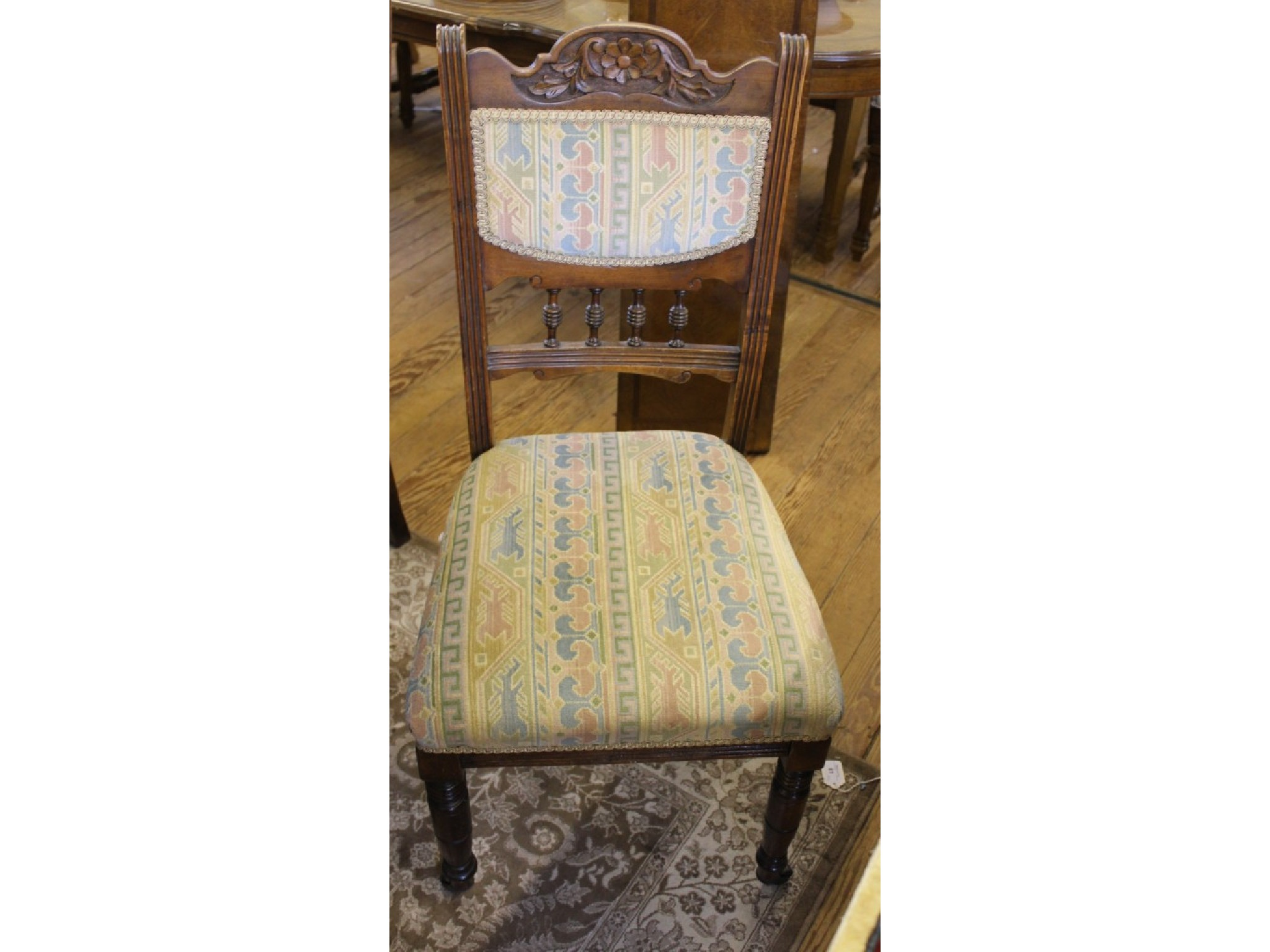 Four late Victorian dining chairs with padded spindle turned backs, ring turned legs and castors to front