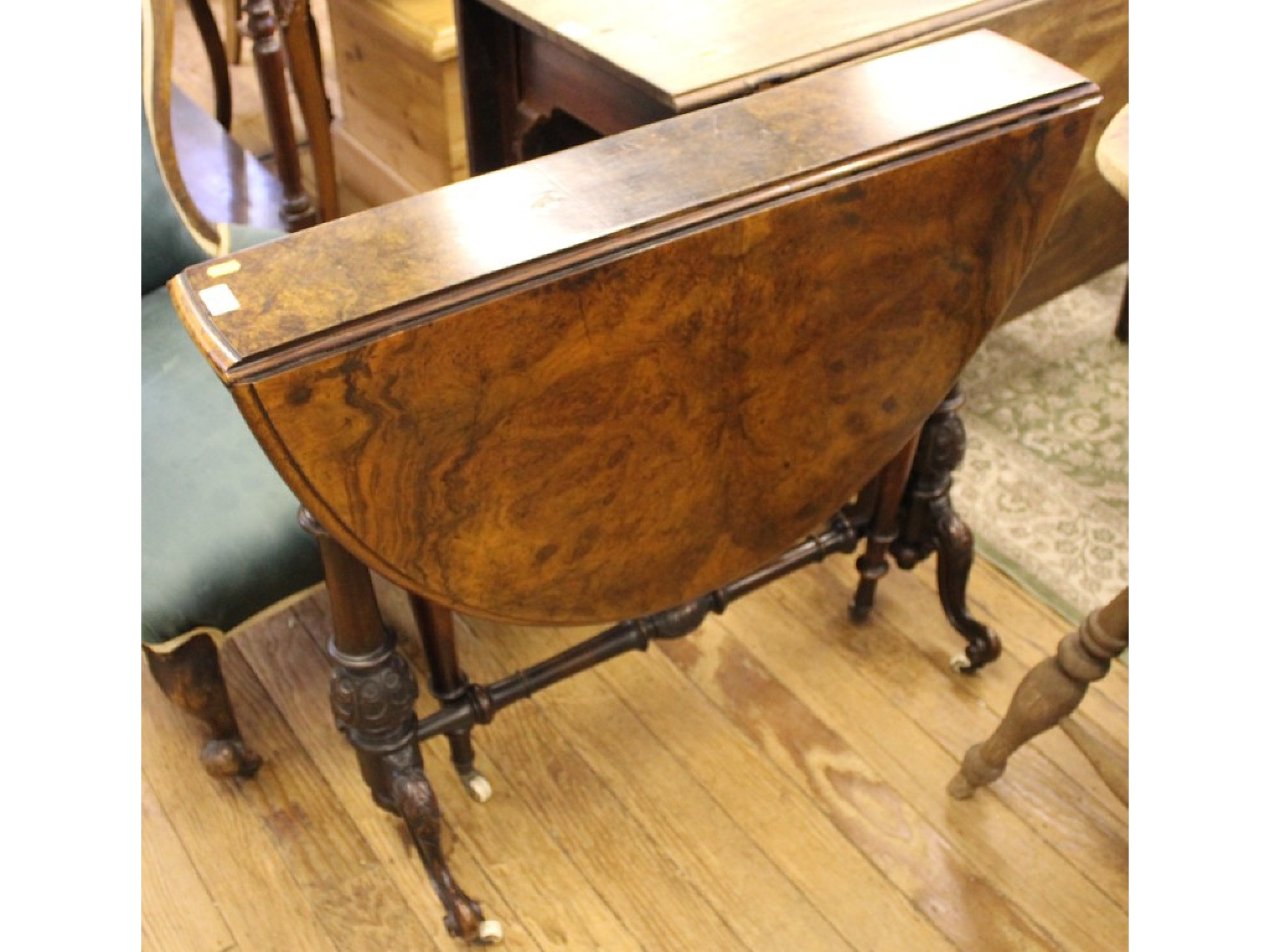 A late Victorian burr walnut Sutherland table, the oval top on turned and carved columns, and moulded cabriole legs