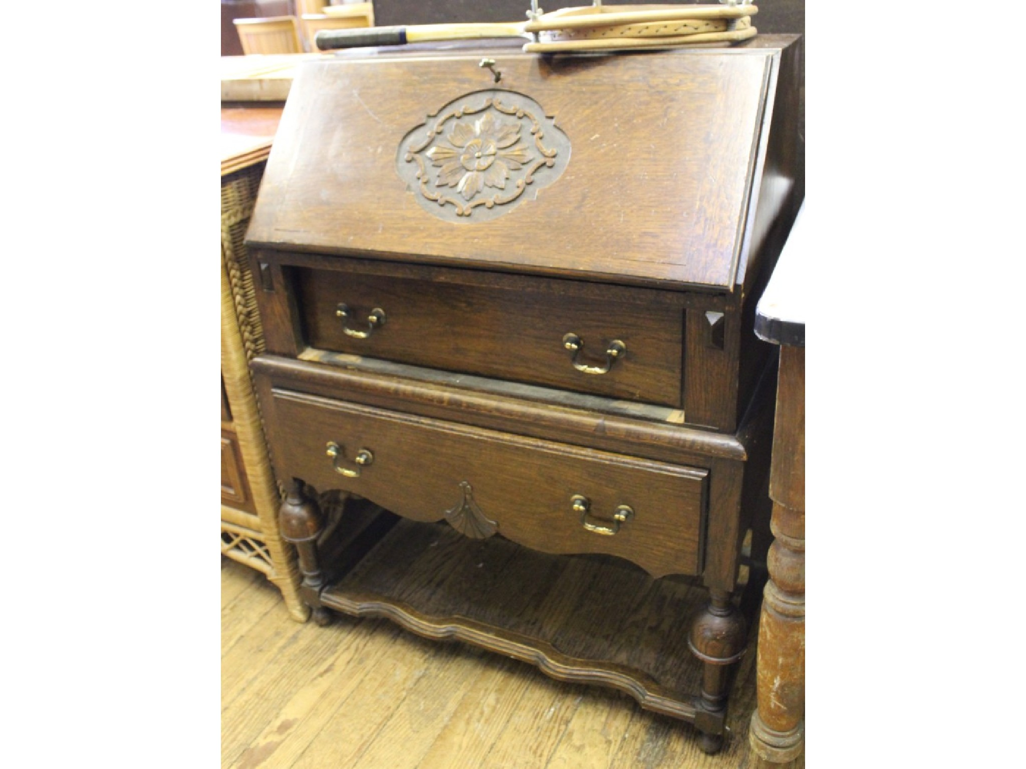 An oak bureau with carved slope, two drawers and turned legs with stretchers, and two painted bedside tables