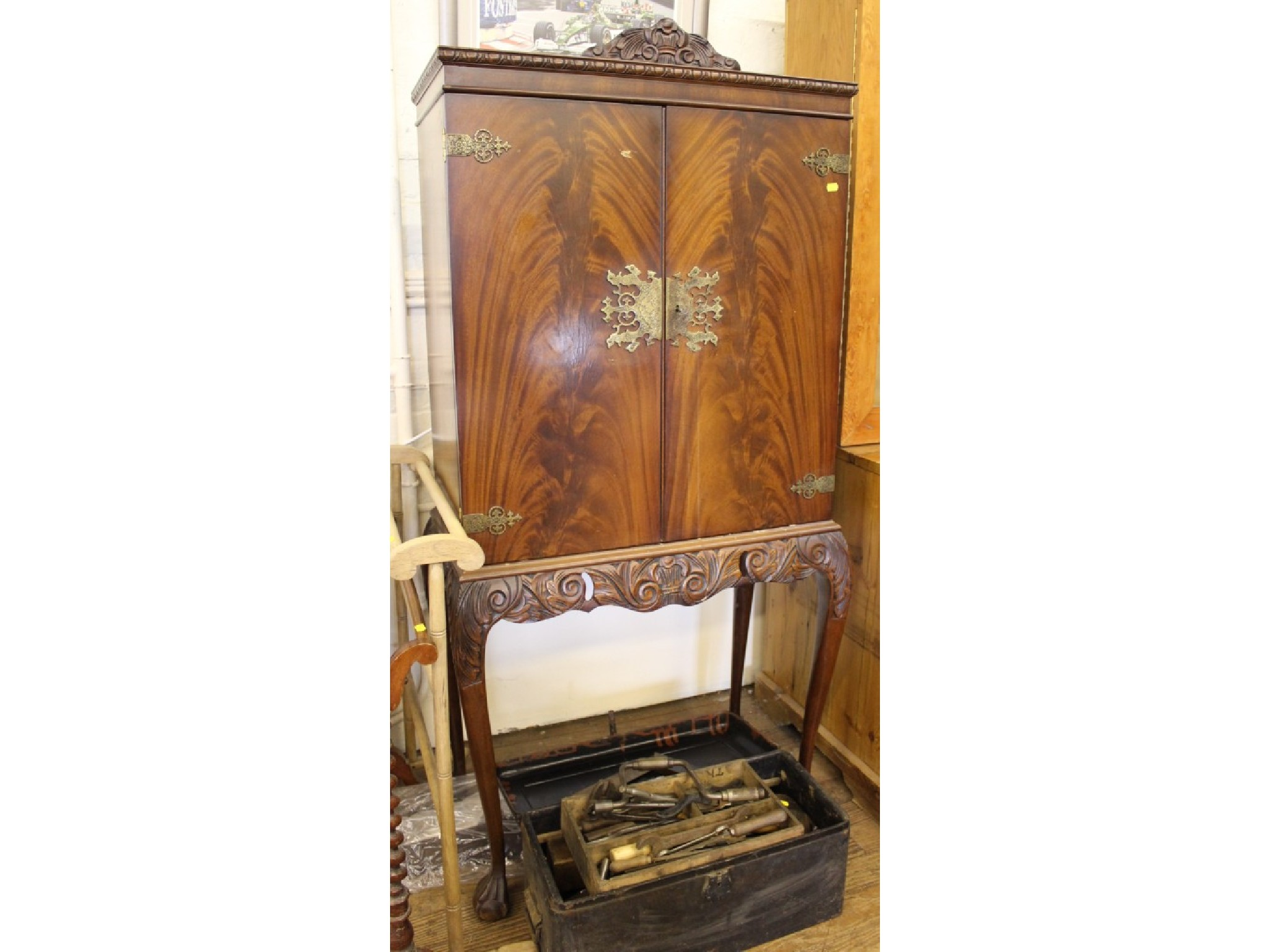 A mahogany veneered cocktail cabinet on carved cabriole legs with ball and claw feet