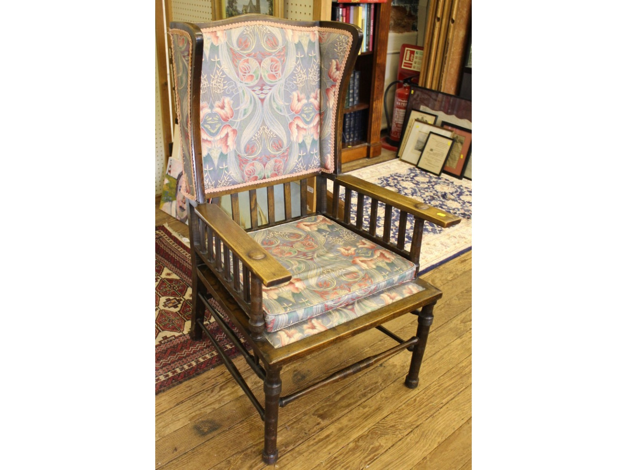 An Arts and Crafts style stained ash armchair, the upholstered back and wings over rail supports and upholstered seat on ring tu