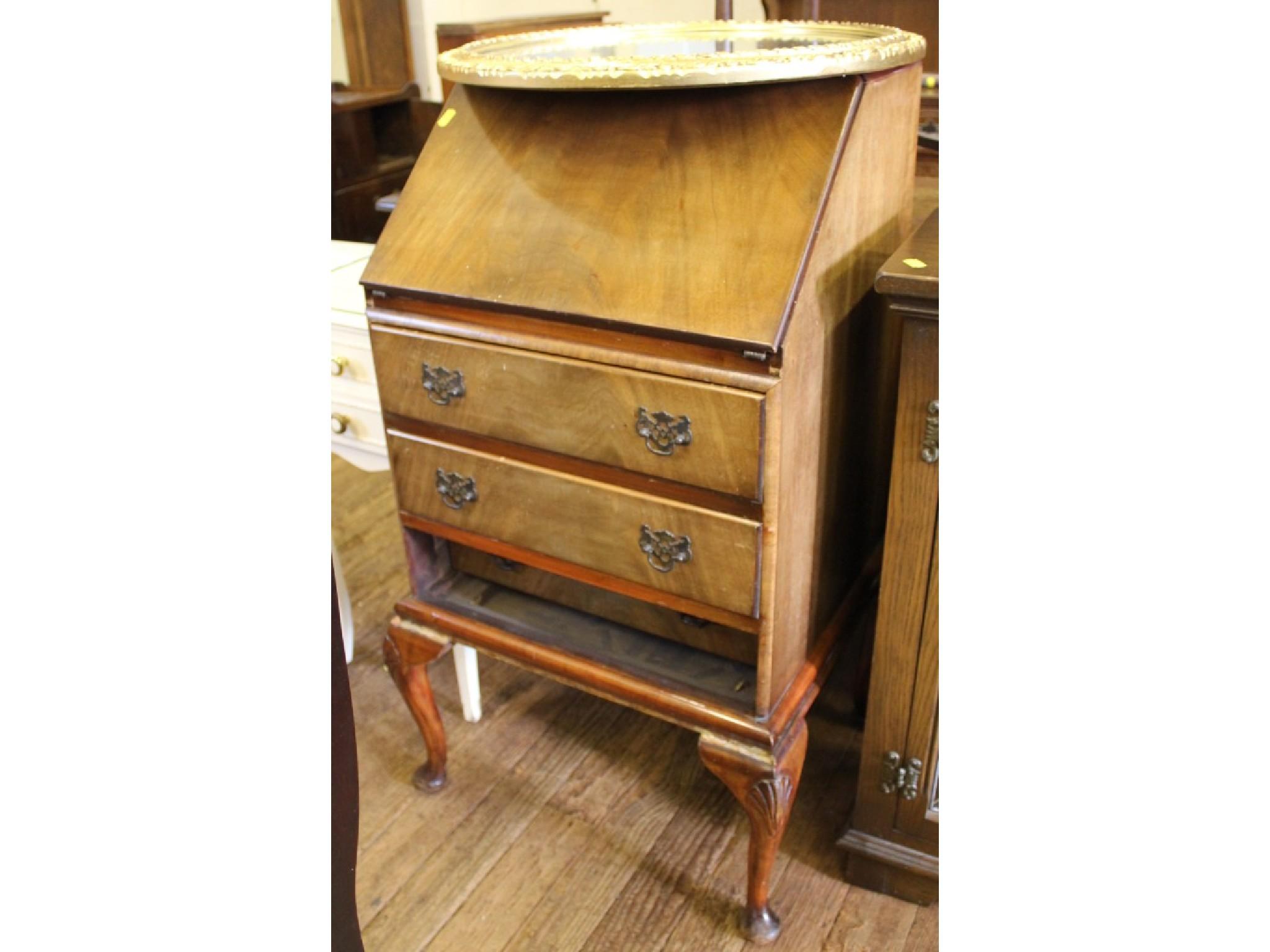 A walnut veneered bureau with three drawers and cabriole legs, Harvey Nichols label, 52cm wide, and a giltwood circular wall mir