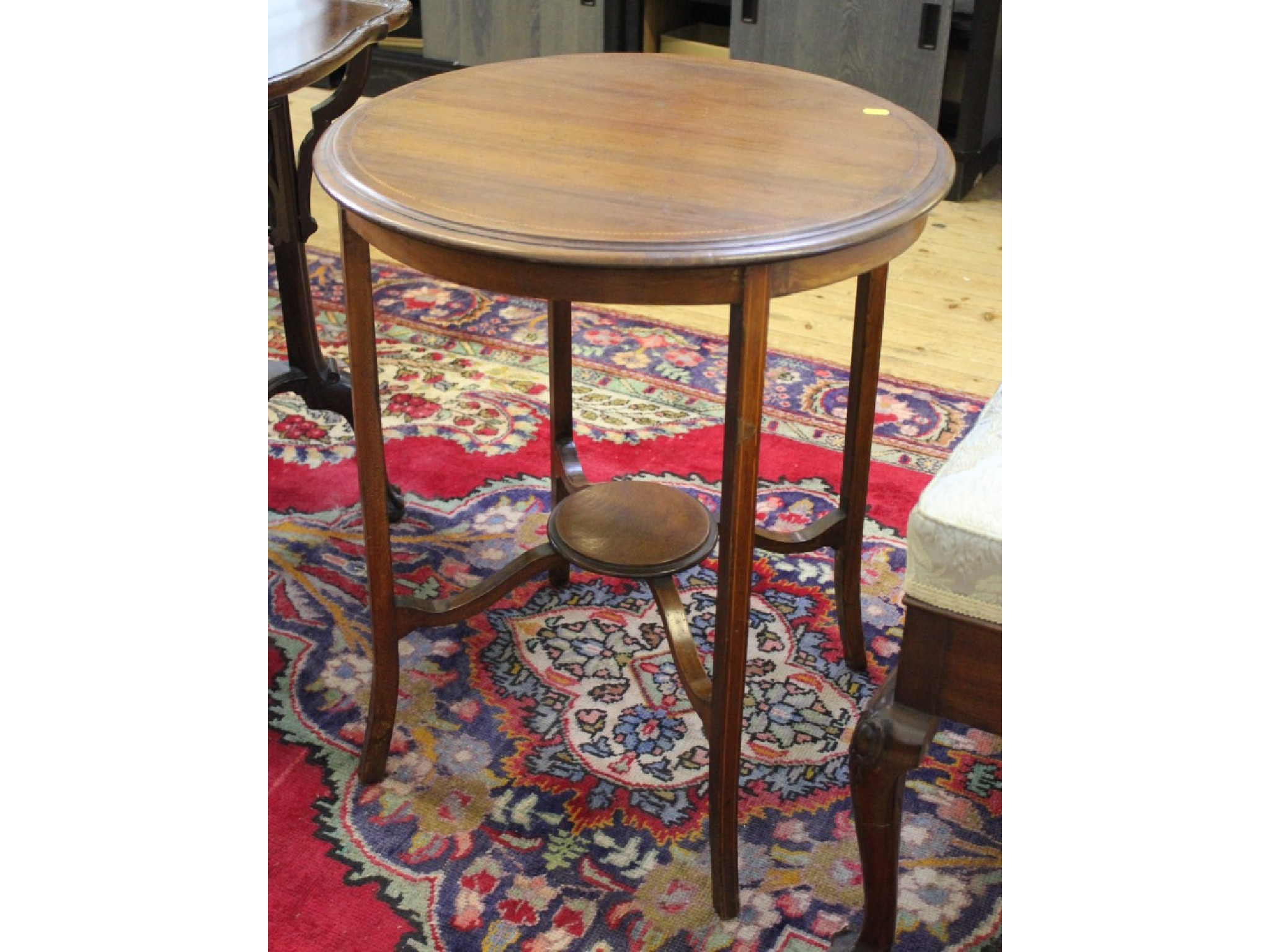 An Edwardian mahogany circular occasional table with chevron banded top, outsplayed legs and circular undertier