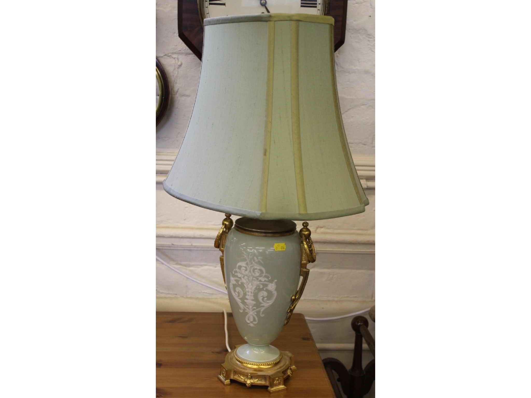 A gilt metal mounted and ceramic table top lamp in the French style, the green tapering vase with cameo style Roman figure