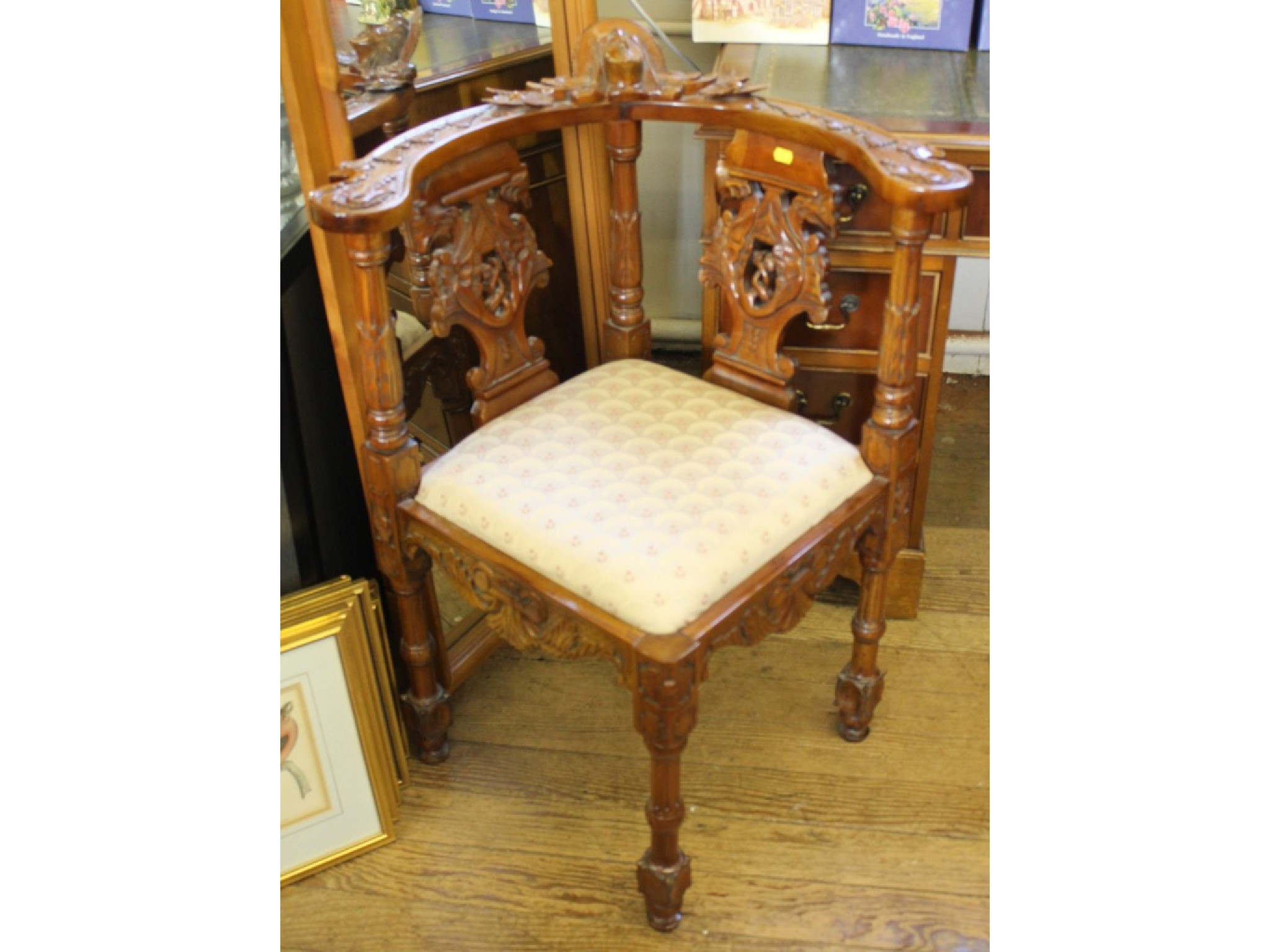 An ornate stained wood corner chair, the flat top rail carved with a mask over pierced splats and carved turned supports