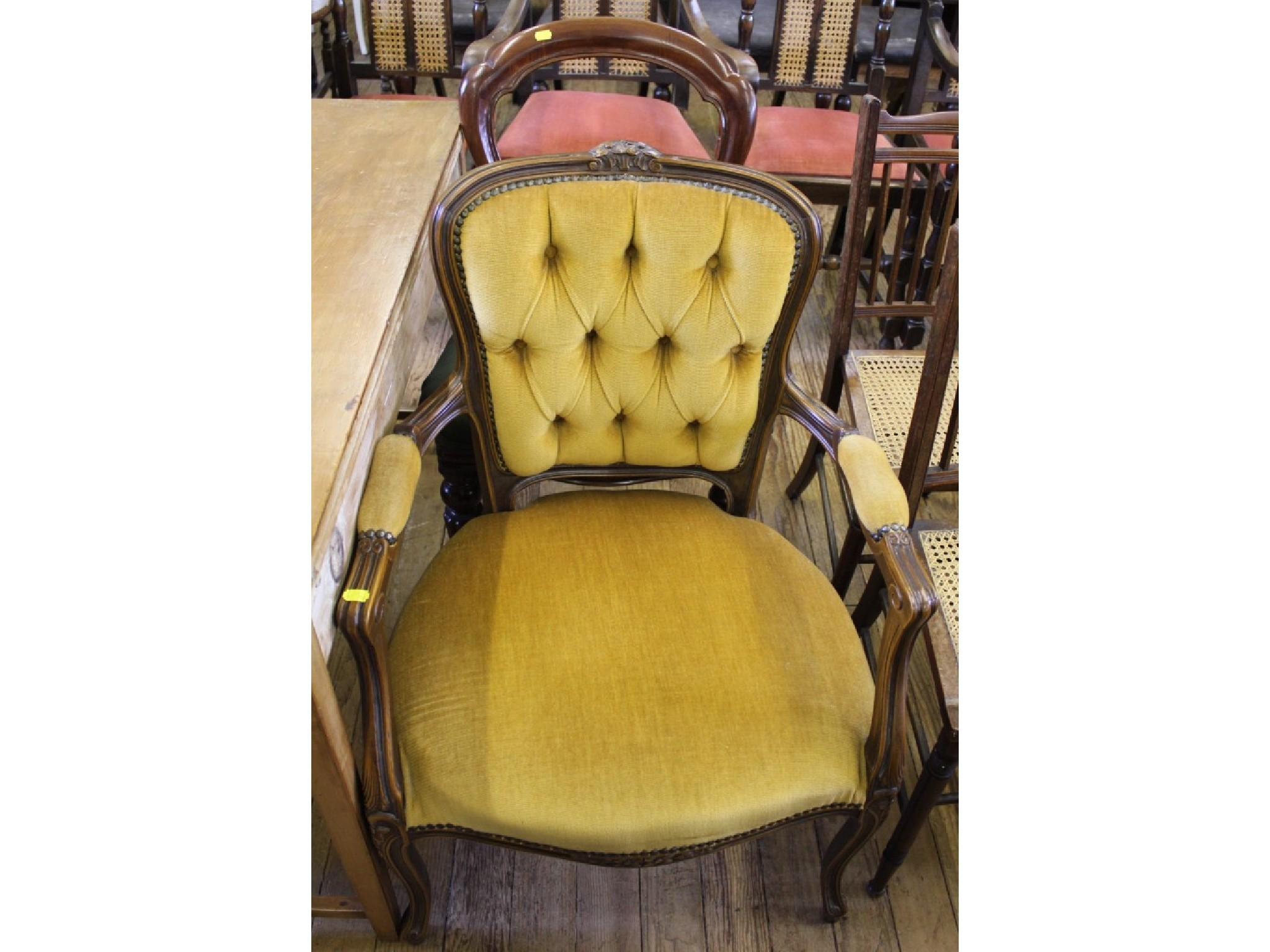 A French style open armchair, the floral carved top rail over a button upholstered back and moulded cabriole legs, and a Victori