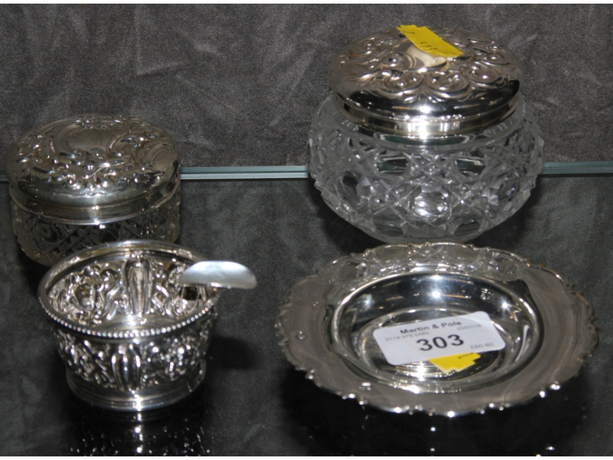 A collection of four pieces of silver, to include ash tray, two silver lidded glass jars, etc