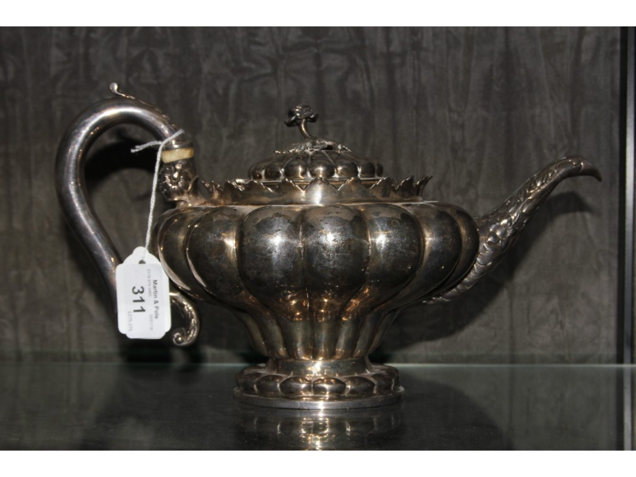 A Georgian silver tea pot of melon form on single foot