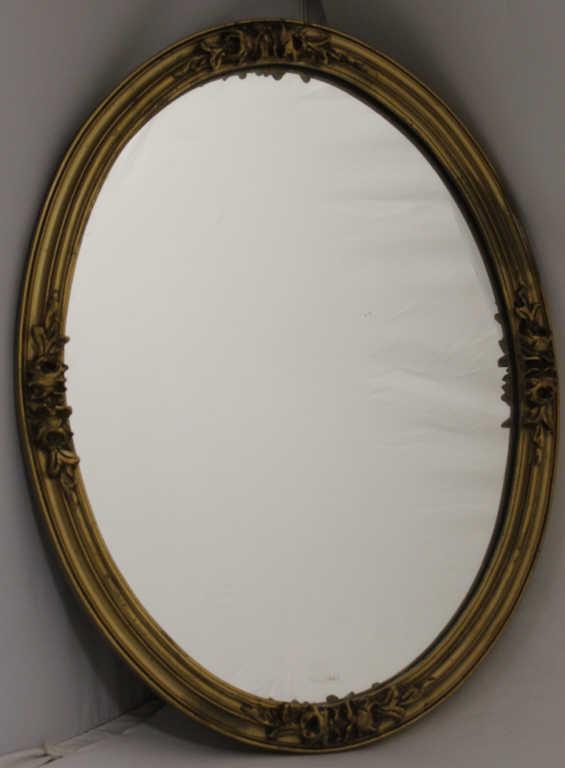 Miroir ovale en bois doré, à décor de fleurettes