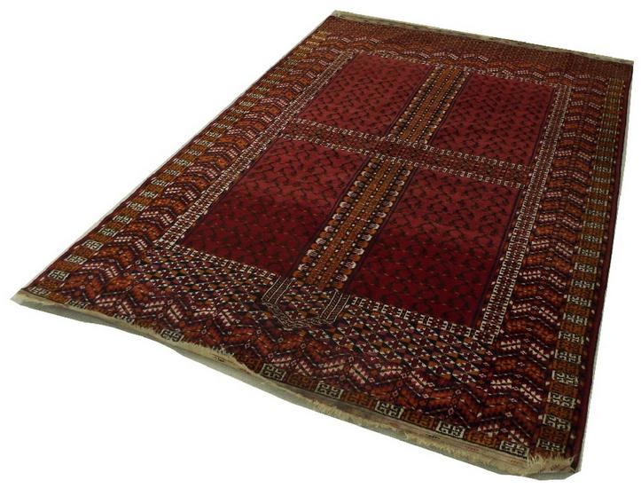 Persian type floor rug decorated with various geometric panels upon a deep red ground