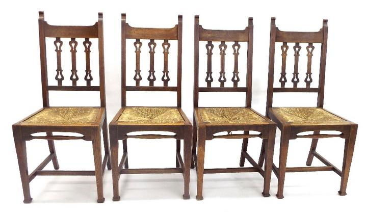 Set of four Arts & Crafts ecclesiastical dining chairs with three pierced vertical splats and drop-in strung seats