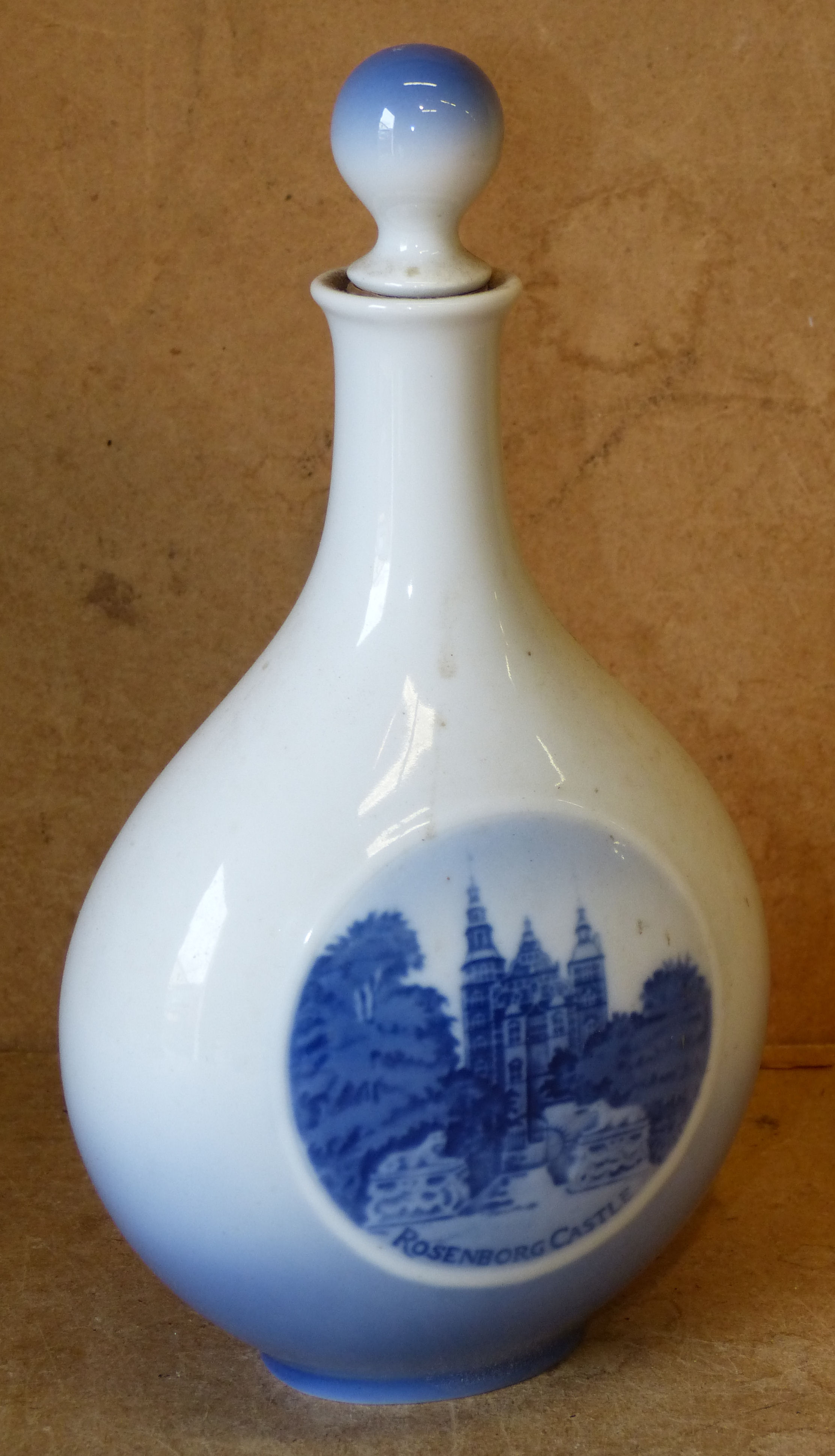 A Royal Copenhagen Oval Bulbous Thin Necked Bottle with stopper on blue