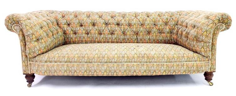 Late 19th/early 20th century Chesterfield sofa with darted upholstery and turned front legs on castors