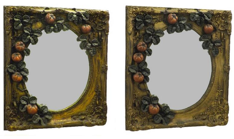 Decorative pair of heavy relief decorated wall mirrors each fitted with an oval mirror plate framed by fruiting vines upon a typ