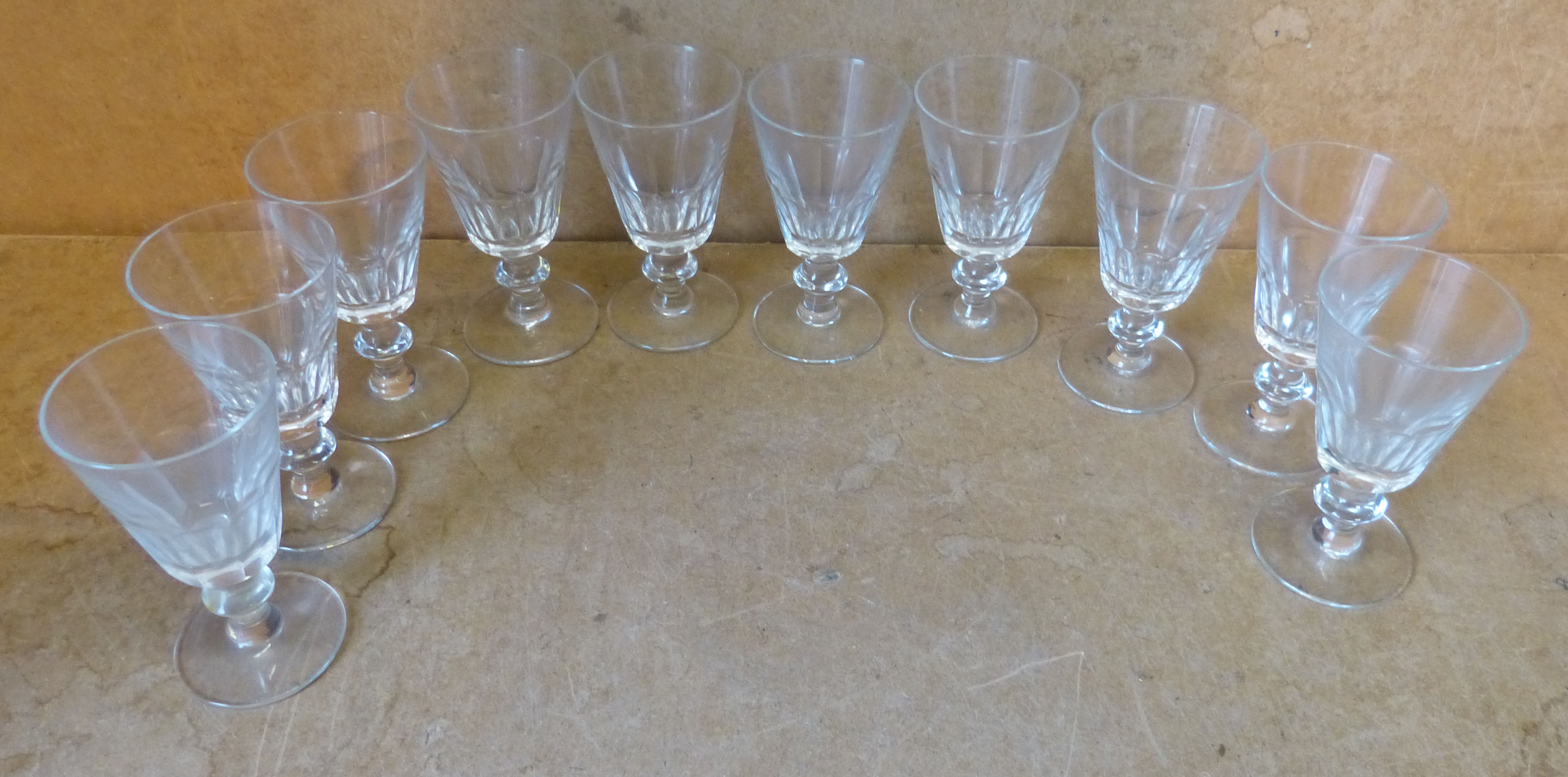 A Set of 10 Trumpet Shape Drinking Glasses having thumb pattern decoration on knob stems with round bases