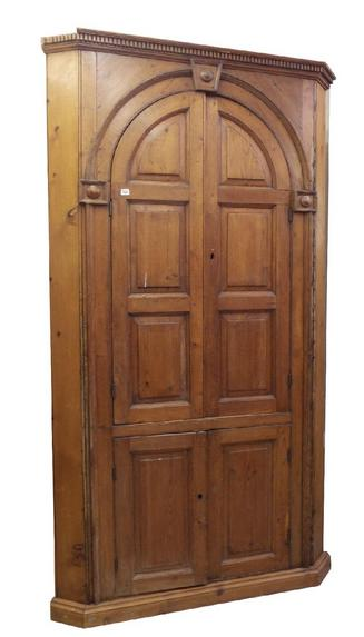 Antique pine corner cabinet, with arched panelled doors enclosing a shelved interior, over two further panelled doors