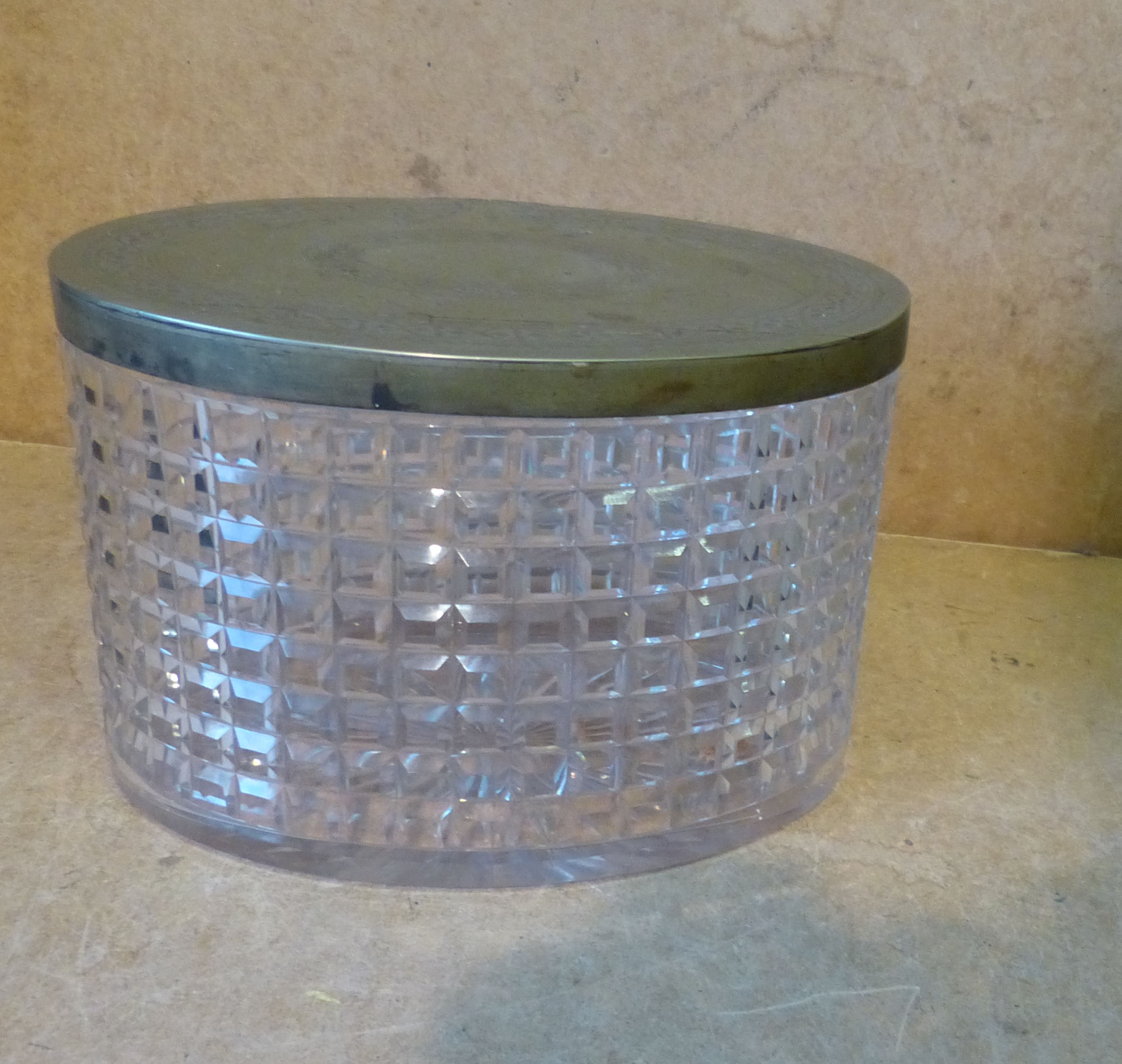 A Cut Glass Oval Biscuit Barrel having silver plated hinged lid, on star cut base